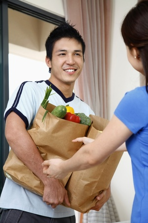 Woman helping man with groceries photo