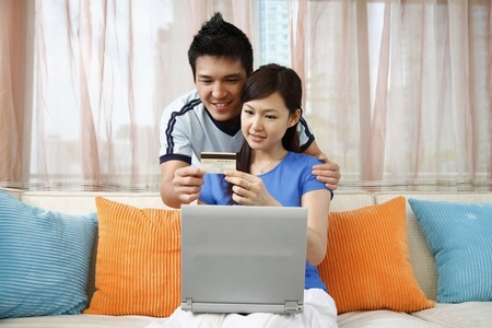holding head: Man and woman holding credit card, shopping online