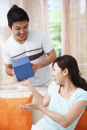 Woman receiving gift from man photo