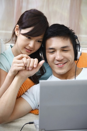 Man and woman using laptop, man with headphones photo