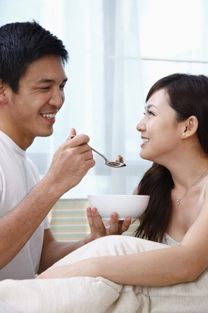 Man feeding woman cereal photo