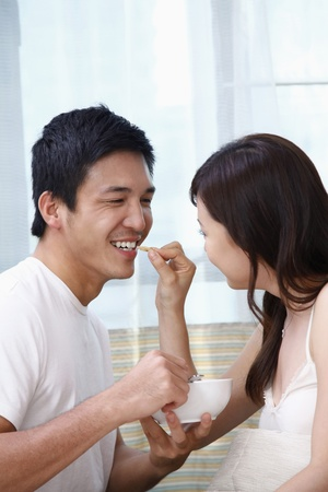 feed up: Woman feeding man cereal Stock Photo