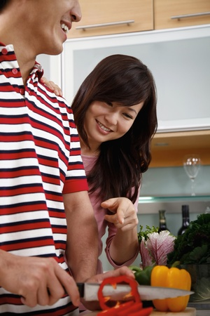 Man preparing a meal, woman pointing at the vegetable photo