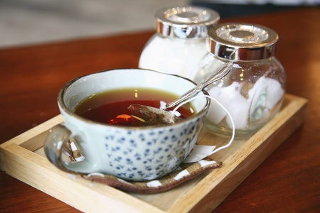 A cup of tea with sugar cubes on a wooden tray