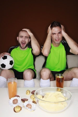 Men touching their heads with disappointment while watching football match Stock Photo - 8981114