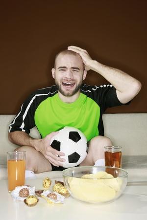 desilusion: Hombre tocando la cabeza con decepci�n mirando un partido de f�tbol en casa
