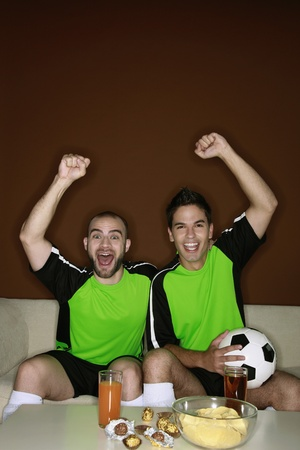 Men cheering while watching football match  photo
