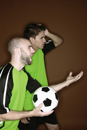 Men touching their heads with disappointment while watching football match photo