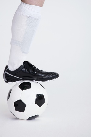 Man stepping on a football photo