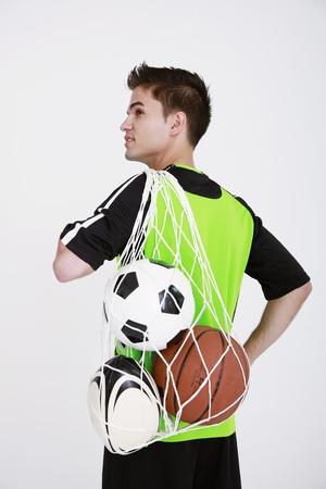Hombre cargando una red de bolas en su espalda Foto de archivo - 8981012
