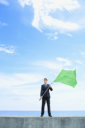 Businessman holding a green flag
