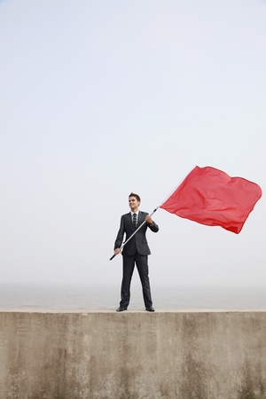 Businessman holding a red flag photo