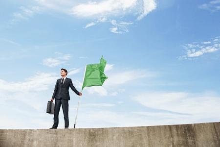 Businessman holding a green flag photo