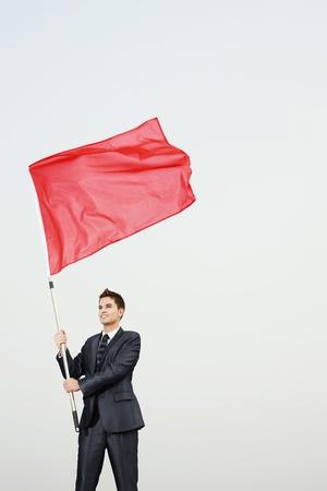 Businessman waving a red flag photo