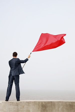Businessman waving a red flag photo