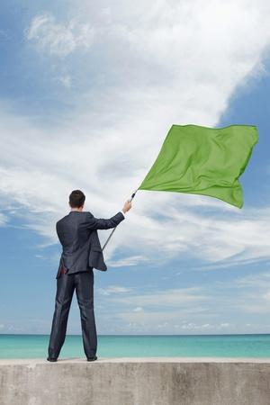 Businessman waving a green flag photo