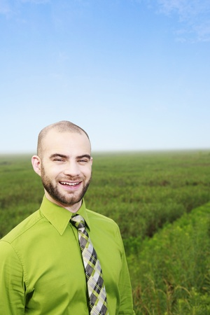 Businessman in green with field in the background photo