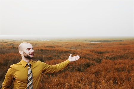 Businessman with arm outstretched, green field in the background photo