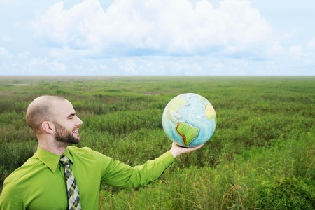 Businessman with arm outstretched holding a globe photo