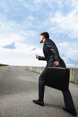 walking alone: Businessman with bag walking on an empty road Stock Photo