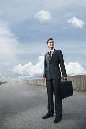Businessman with bag standing on an empty road photo