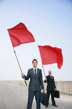 Businessmen with bags and red flags photo