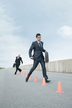 Businessmen running in between traffic cones photo