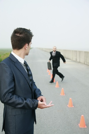 Businessman running in between traffic cones, another businessman watching Stock Photo - 8981232
