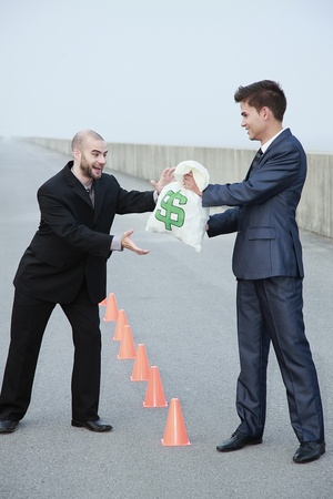 Businessman receiving a bag of money from another businessman Stock Photo - 8981338