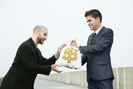 Businessman receiving a bag of money from another businessman