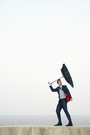 viento soplando: Hombre de negocios con un paraguas, viento su paraguas lejos
