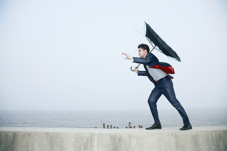 struggling: Businessman with an umbrella, wind blowing his umbrella away Stock Photo