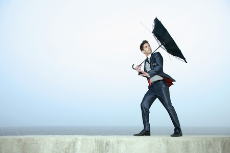 blowing wind: Businessman with an umbrella, wind blowing his umbrella away Stock Photo