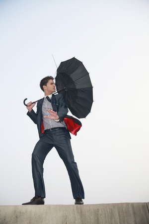blowing out: Businessman with an umbrella, wind blowing his umbrella away Stock Photo
