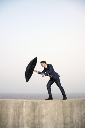 Businessman with an umbrella, wind blowing his umbrella away Stock Photo