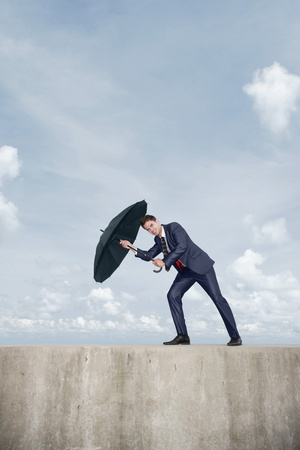 Businessman with an umbrella, wind blowing his umbrella away photo