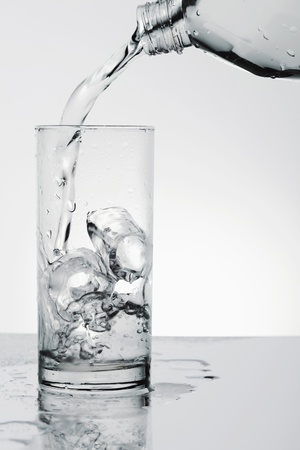 Pouring water into drinking glass with ice photo