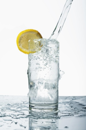 Pouring water into drinking glass with ice Stock Photo - 8980837