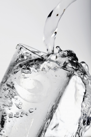 Pouring water into drinking glass with ice Stock Photo - 8980877