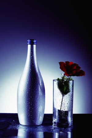 Wet bottle and rose in drinking glass photo