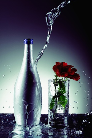 Water pouring on bottle with rose in drinking glass at the side photo