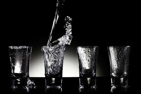sparo: Acqua versando in bicchierini Archivio Fotografico