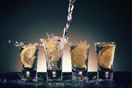 Gießen Wodka in Shot Gläser mit Zitrone