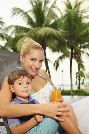 Woman and boy sitting on lounge chair smiling photo