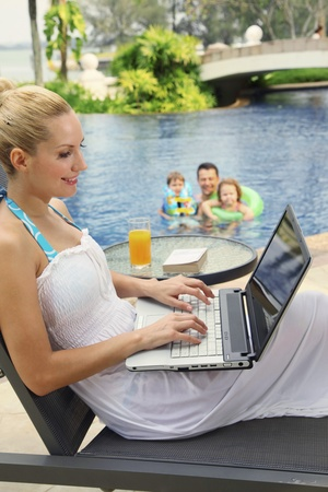 Woman using laptop on lounge chair photo