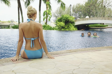 Woman in bikini sitting at the edge of pool watching her family swim photo