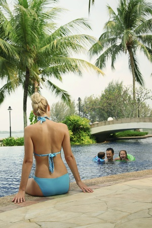 swimming pool float: Woman in bikini sitting at the edge of pool watching her family swim Stock Photo