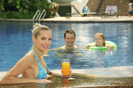 Woman with a glass of orange juice at the edge of pool Stock Photo