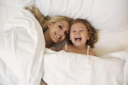 girl lying down: Mujer y ni�a acostado en la cama sonriente