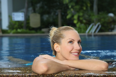 Woman resting head on arm at the edge of pool photo